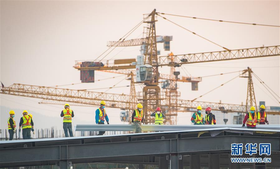 2月4日,在武汉雷神山医院建设工地,来自中建三局的建设工人在加紧施工。<br/>当日,武汉雷神山医院建设进入冲刺决战阶段,预计2月5日具备交付条件。 截至2月4日12时,病房隔离区箱式板房吊装已完成96.5%,同步进行安装及装修施工;医技楼钢结构安装、屋面板安装基本完成,正在进行各功能区内装和医疗设备安装施工,其中检验设备及CT等已进场,准备进行调试;污水处理站设备及管道安装已完成;垃圾焚烧站已完成结构施工;路面硬化已完成50%。<br/>新华社记者 肖艺九 摄<br/>