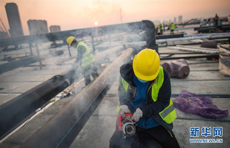 2月4日,在武汉雷神山医院建设工地,来自中建三局的建设工人在加紧施工。新华社记者 肖艺九 摄
