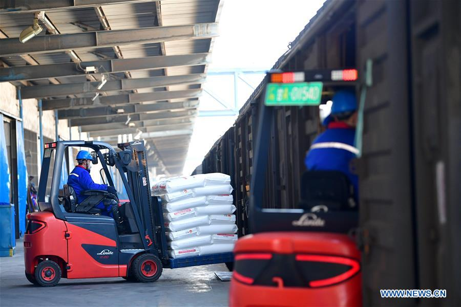 Employees transfer polypropylene material for medical use to a cargo train with forklifts in Lanzhou, northwest China's Gansu Province, Feb. 12, 2020. Lanzhou Petrochemical Company has rushed to work to meet the increasing need of medical material after the novel coronavirus outbreak. (Xinhua/Chen Bin)<br/>