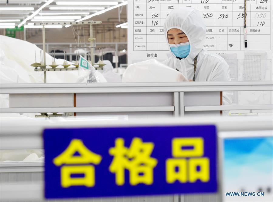 A worker examines protective suits at a workshop in a company in Ningjin County, north China's Hebei Province, Feb. 12, 2020. Many local companies producing protective suits have rushed to work to meet the increasing need of medical material after the novel coronavirus outbreak. (Xinhua/Wang Xiao)<br/>