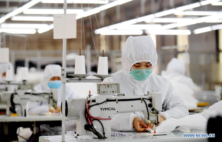 Workers make protective suits at a workshop in a company in Ningjin County, north China's Hebei Province, Feb. 12, 2020. Many local companies producing protective suits have rushed to work to meet the increasing need of medical material after the novel coronavirus outbreak. (Xinhua/Wang Xiao)<br/>