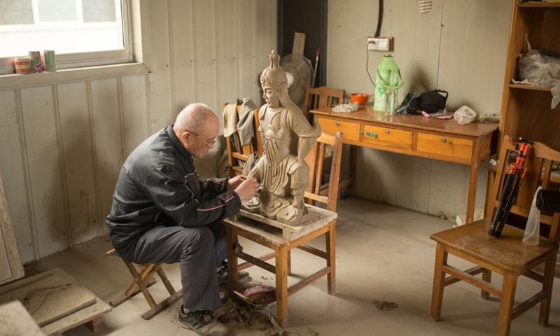 A senior sculptor makes a worrier statue at the Qufu Glazed Tile Factory Co Photo: Shan Jie/GT
